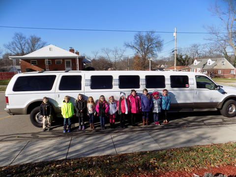 Students stand by white Hummer limo
