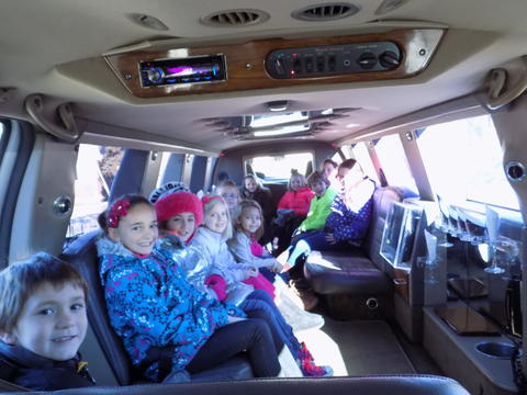 Students sit inside long white Hummer limo