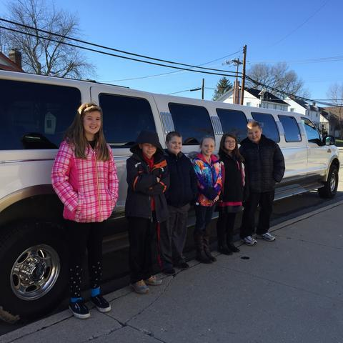 Second group of students pose by limo