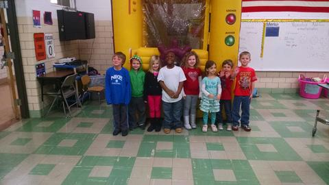 Row of students pose in front of bounce house