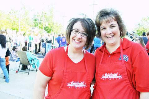 Two adult women wearing red shirts and aprons