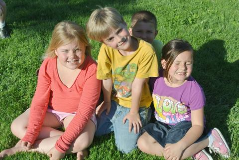 Students sitting in grass smile