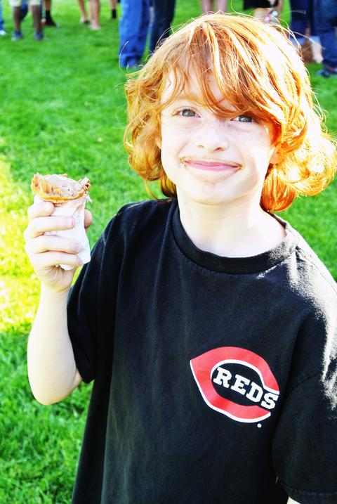 Red-headed boy eats ice cream and smiles