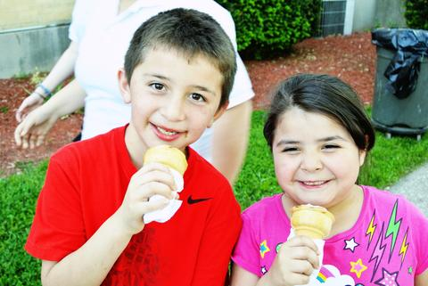 Two students enjoy ice cream and smile