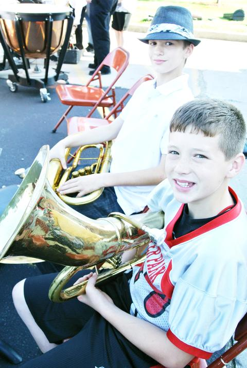 Student musician holds baritone and smiles