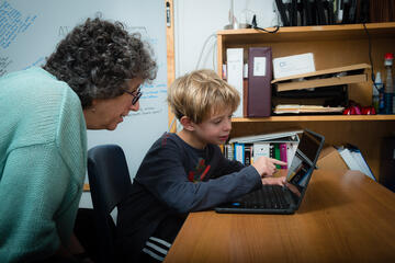 Teacher working with a student using a laptop