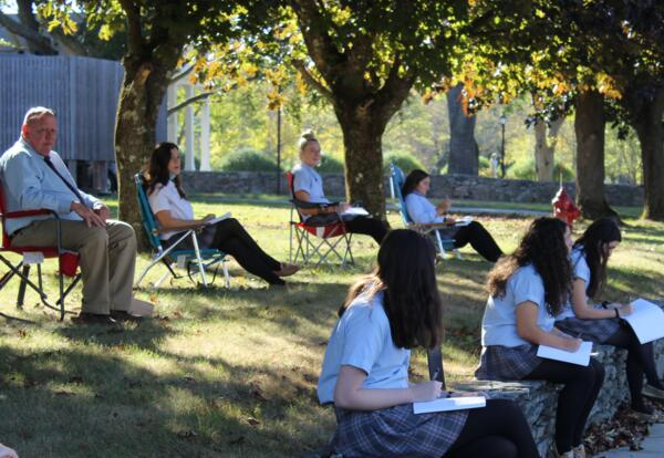 Mr. Ostrye and students writing outdoors