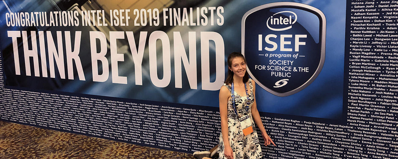 Student stands beside name wall at ISEF 2019