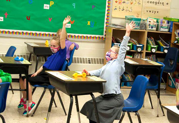 Two elementary school girls raise hands enthusiastically in class.