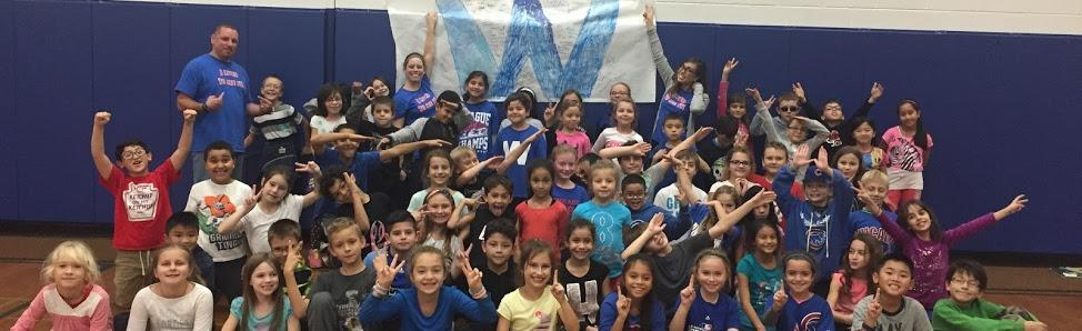Third grade teachers and students posing with a Wrigley Flied W flag