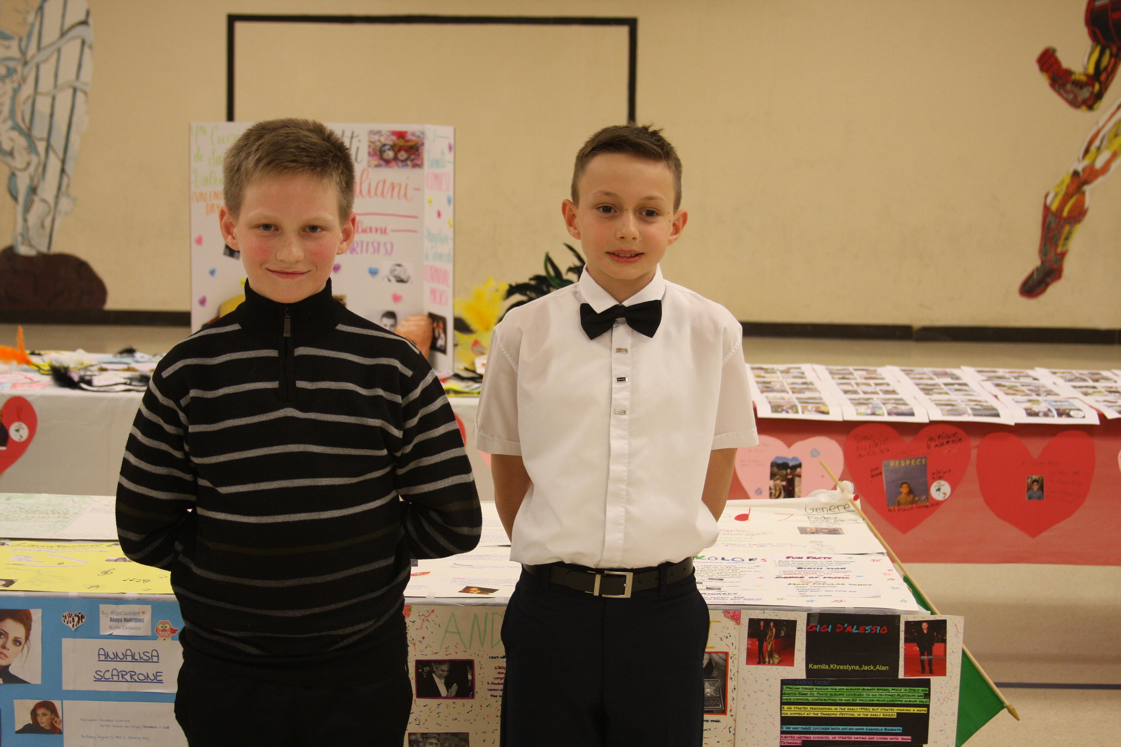 two boy posing in front of their art display