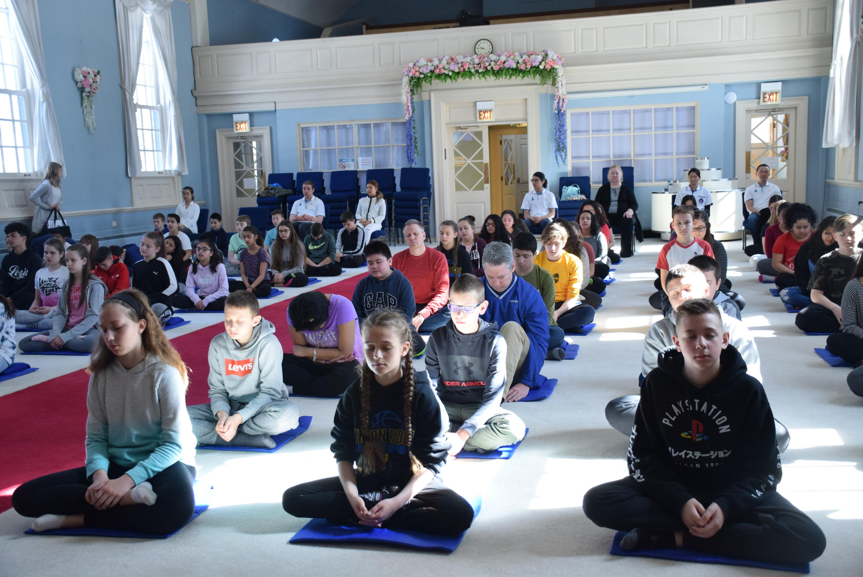 students and teachers in meditation