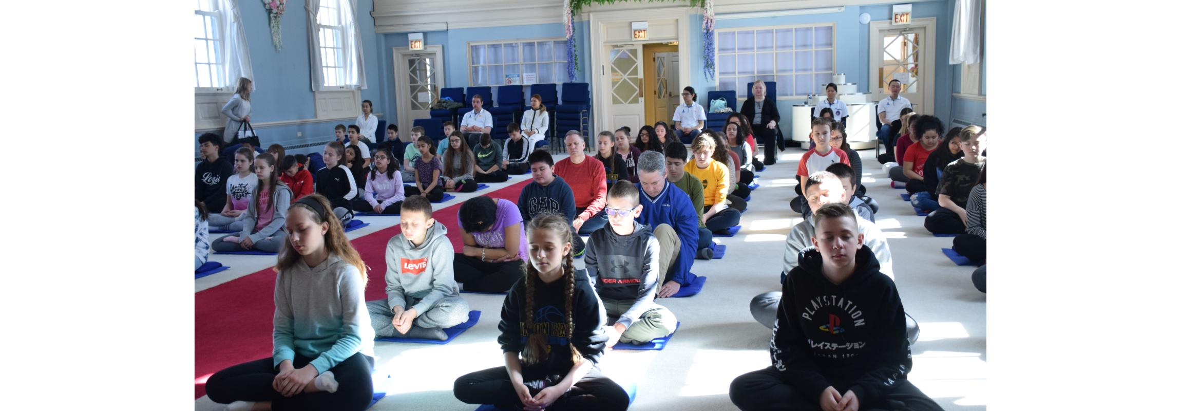 students and teachers meditating