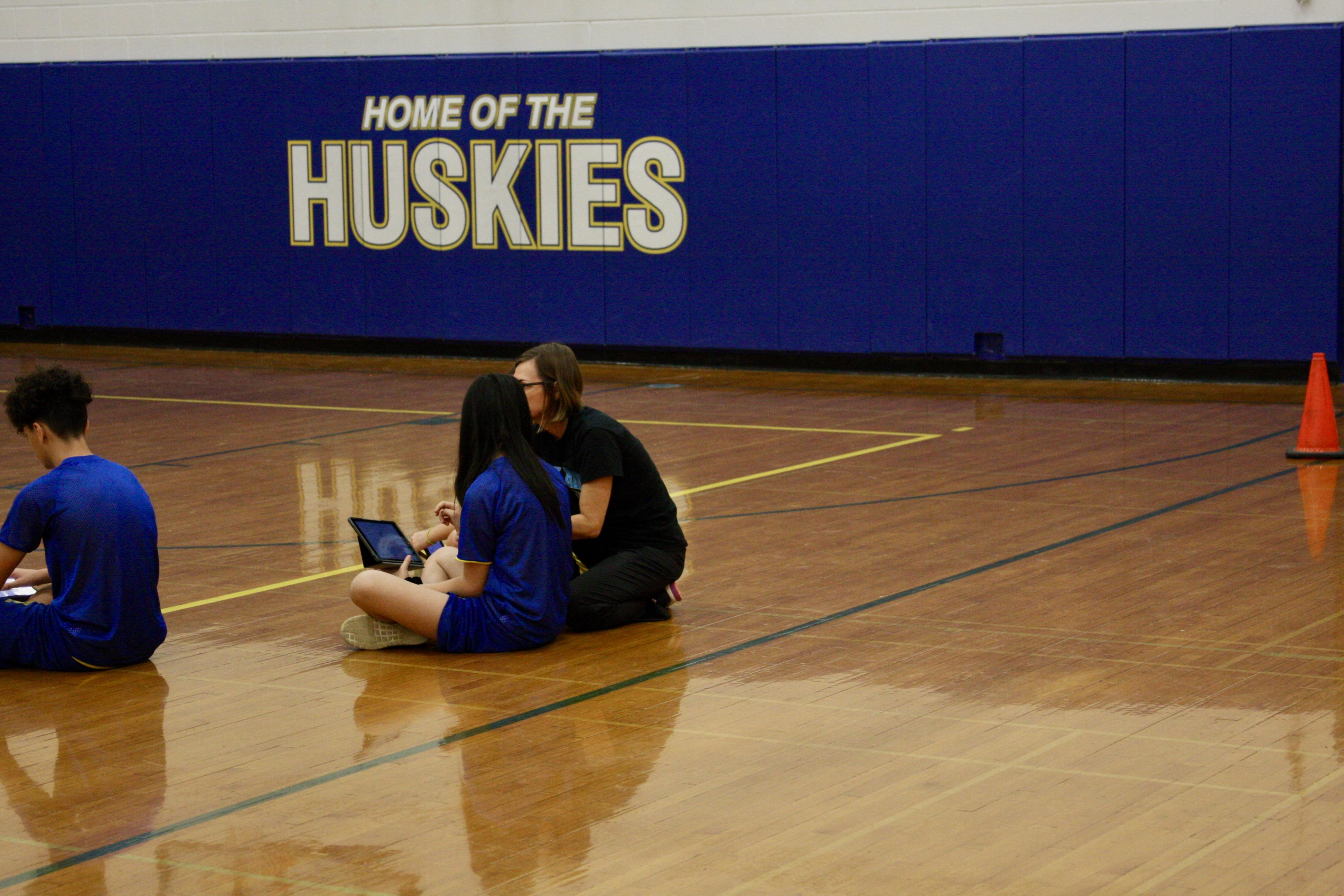 Science teacher working with student during PE class.