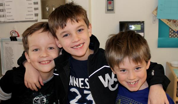 Three boys smiling with arms around each other