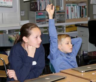 6th Grade Students in class raising hand