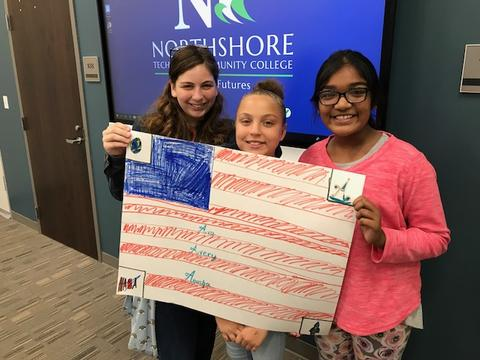 Three students holding a drawing of the American flag