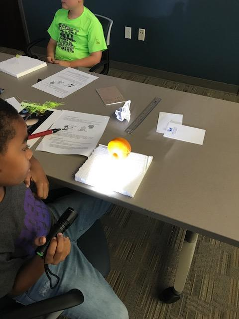Student studying how light is blocked by looking at orange in front of light