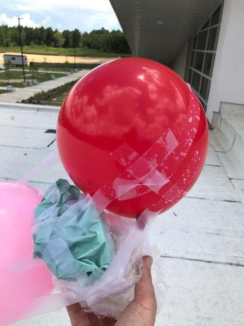 Red balloon attached to egg drop experiment