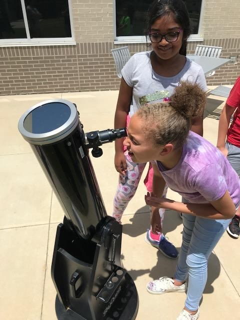 Student looking through a black telescope