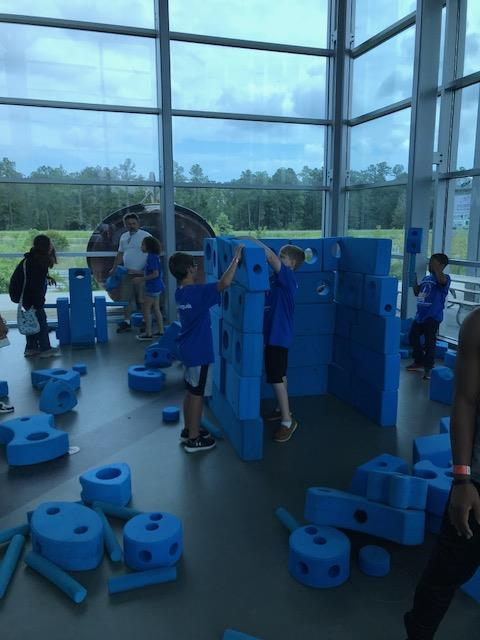 Students making a structure out of blue foam blocks