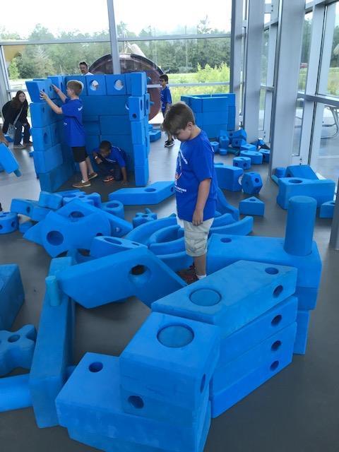 Student standing amidst blue foam blocks