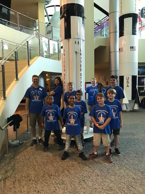 Class in blue t-shirts posing at Science Center