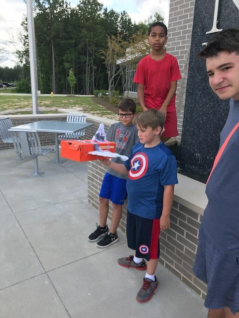 Student holding shoebox glider