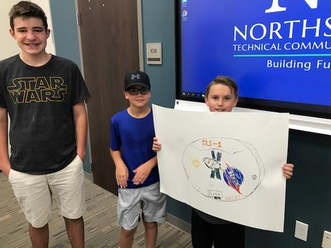 Students holding drawing of a mission patch