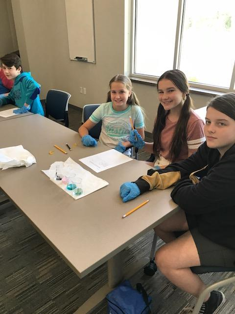 Three female students wearing blue gloves, beakers in front of them