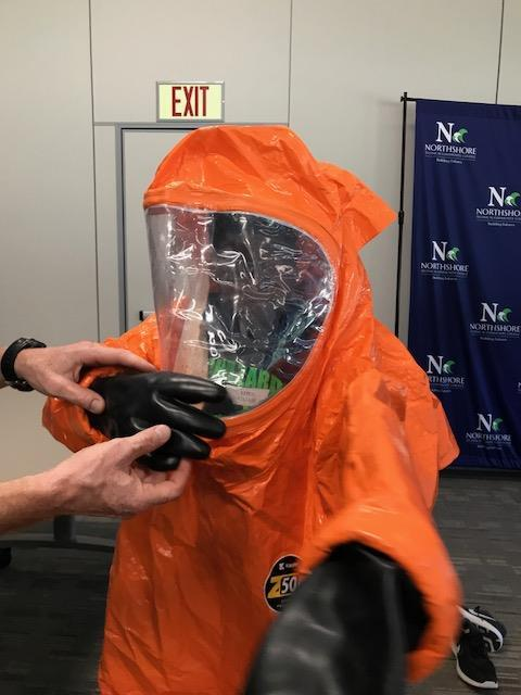 Closeup of person in hazmat suit; with clear face shield and black rubberized gloves