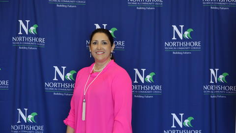 Attendee wearing bright pink top and lanyard poses in front of blue Northshore backdrop