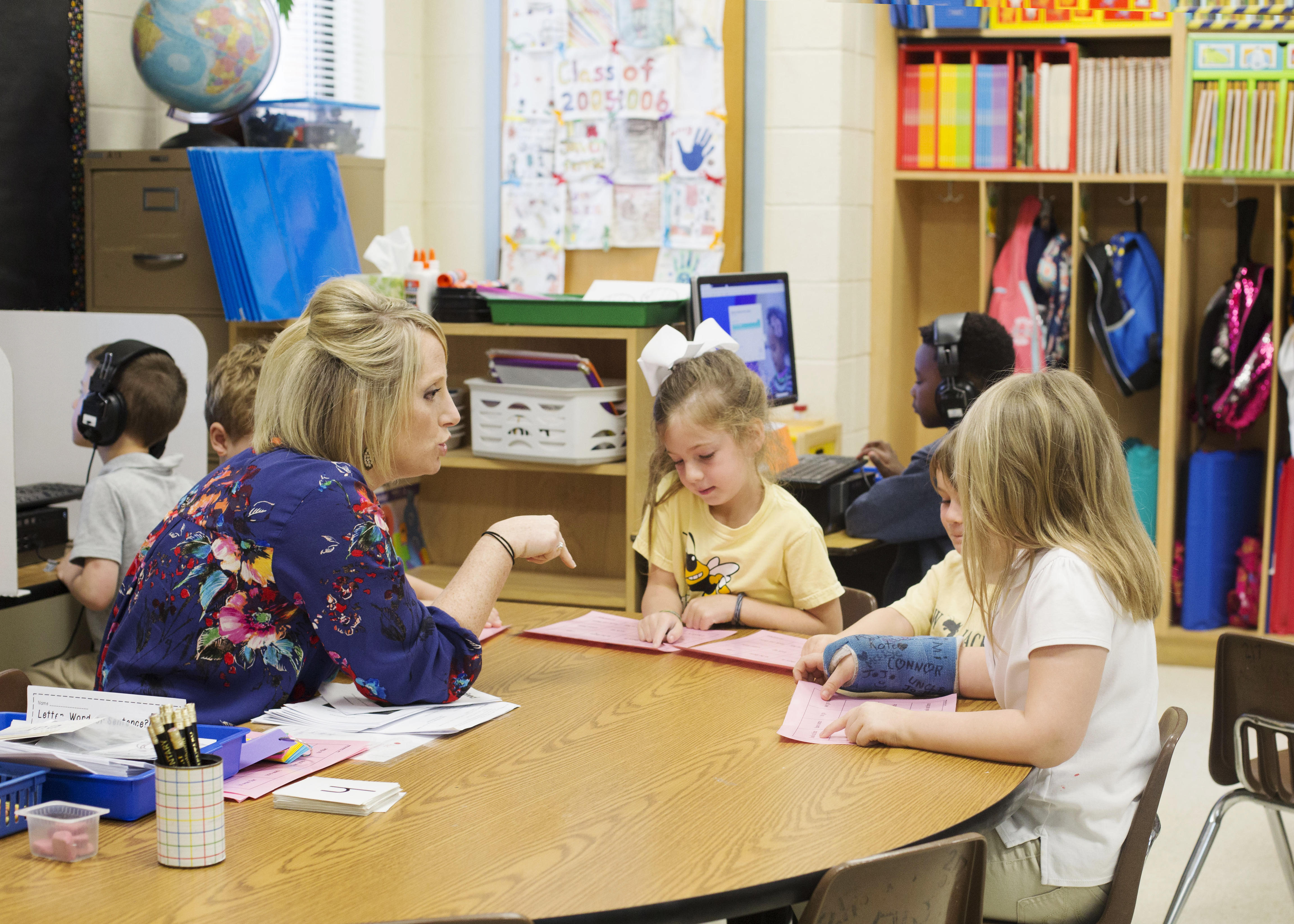 Kindergarten teacher works with students during reading group