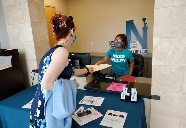 Nunez Community College student worker Chelsey Grossley of New Orleans assists guests at the welcome desk in Nunez's Administration Building. Registration for the Summer and Fall 2021 semesters is open now at Nunez.edu.