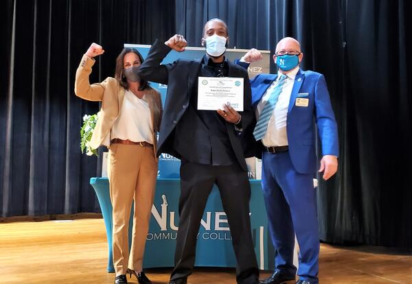 Blake Prout Jr. of Port Sulphur flexes for a picture with Nunez Community College Chancellor Dr. Tina Tinney and Nunez Executive Dean of Continuing Education Lenny Unbehagen after receiving his completion certificate from Venture Global LNG's Will To Skil