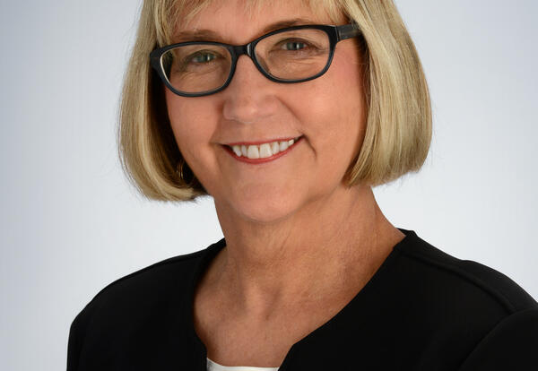 lady with short blonde hair and glasses