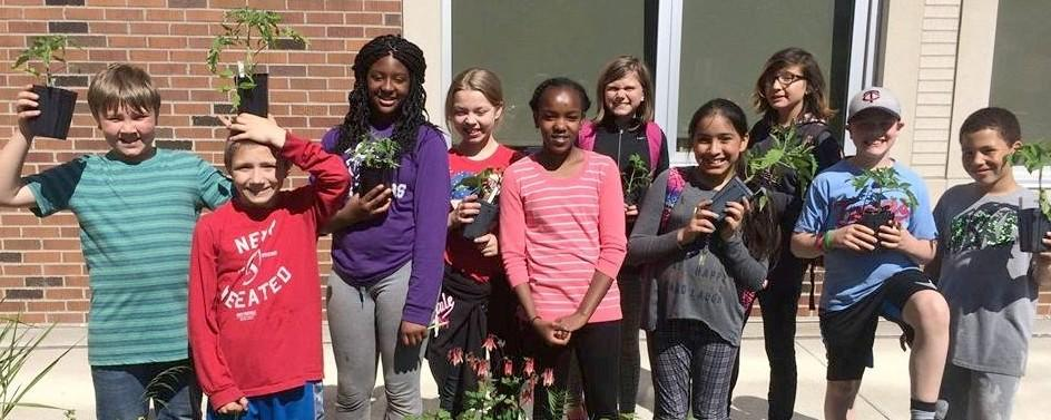 Students holding plants and smiling