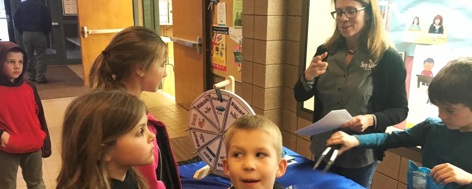 Students spinning wheel at booth