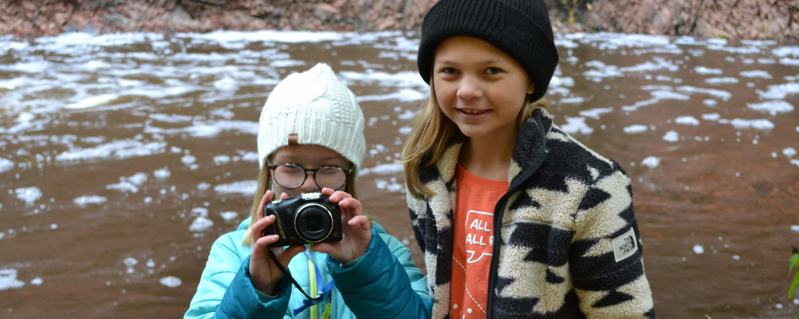 Two students in winter gear; one is holding camera to face