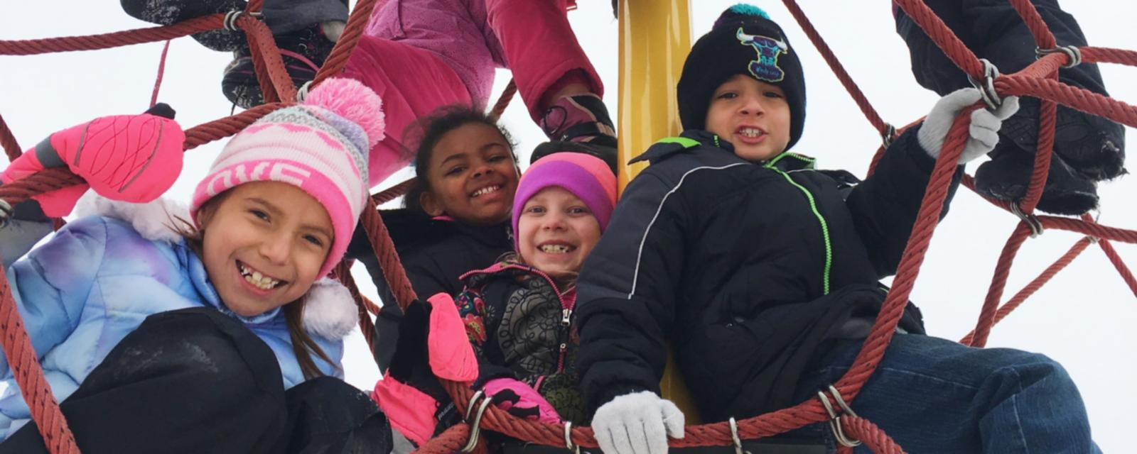 Students in winter gear on playground