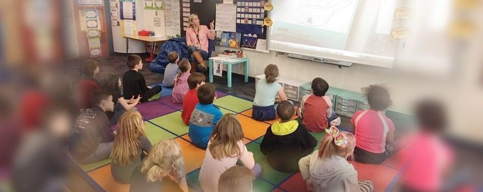 Students sitting on mats, listening to teacher