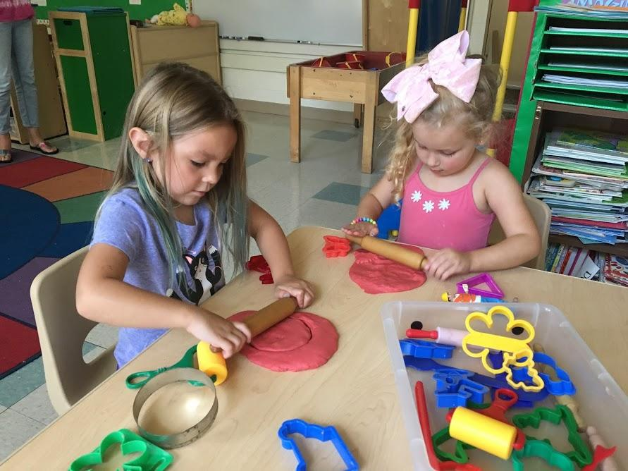 Preschool girls rolling out dough