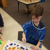 Child using eye dropper to mix watercolors on paper