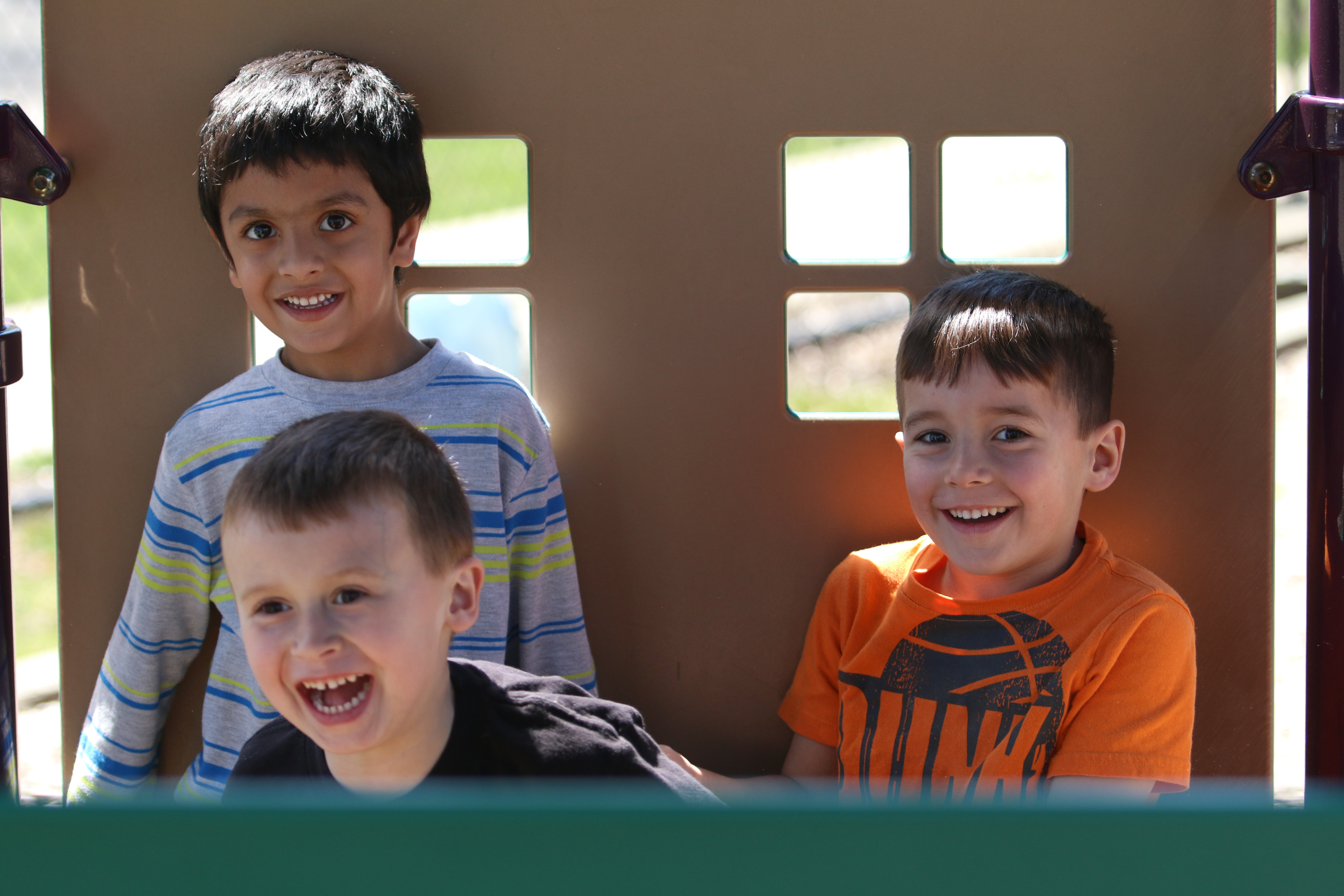 Boys playing in playhouse on preschool playground