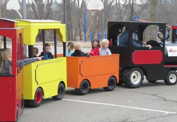 Children riding in a black and red train with 2 cars on the back.  One is yellow one is orange.