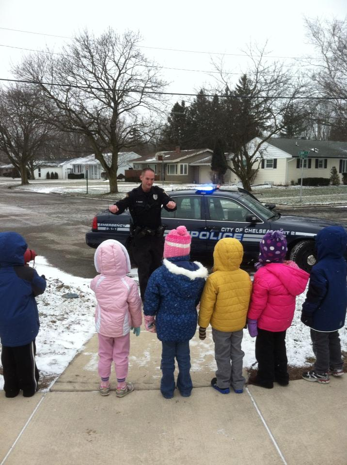 Children outside in snow gear listening to a police officer and looking at a police car.