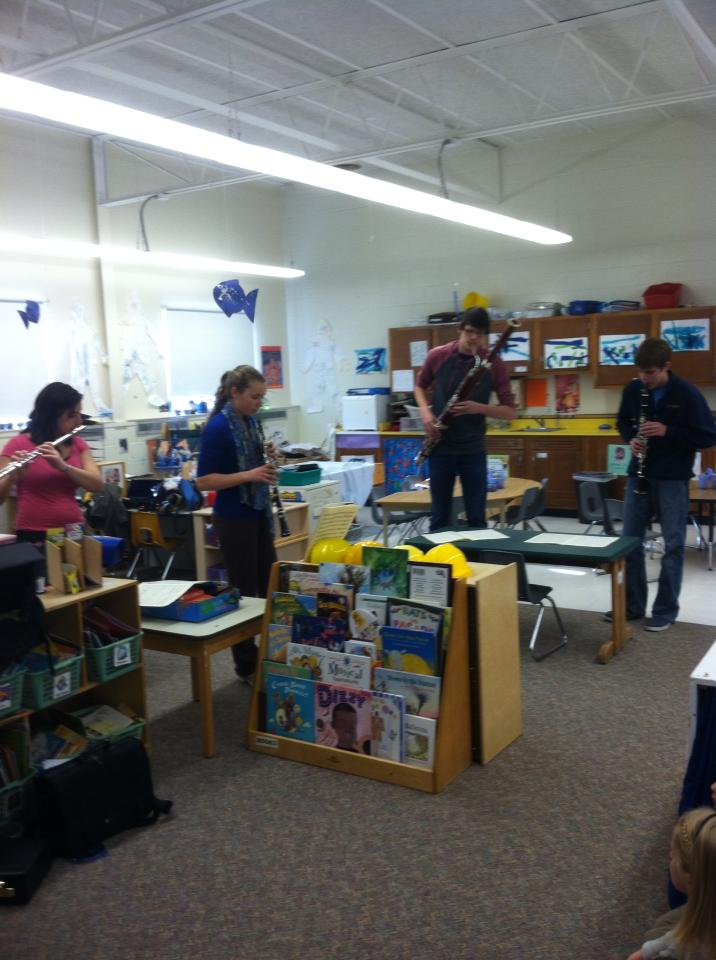 High school students playing instruments in preschool classroom