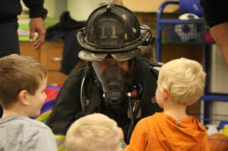 Children looking at a firefighter on his hands and knees with his mask and helmet on.