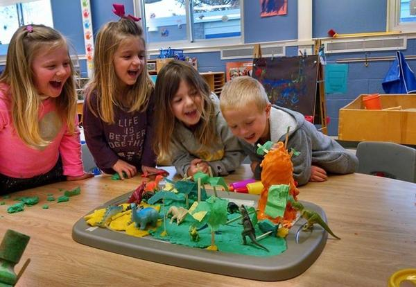 three children looking at a model volcano decorated with small trees and dinosaurs