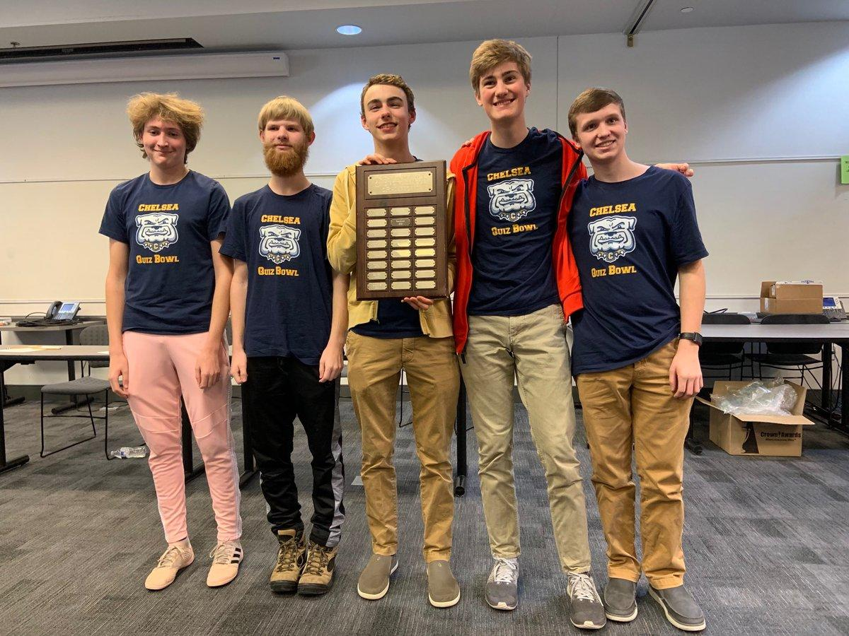 quiz bowl students standing with award